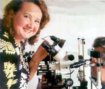Photo of Angela looking through a microscope